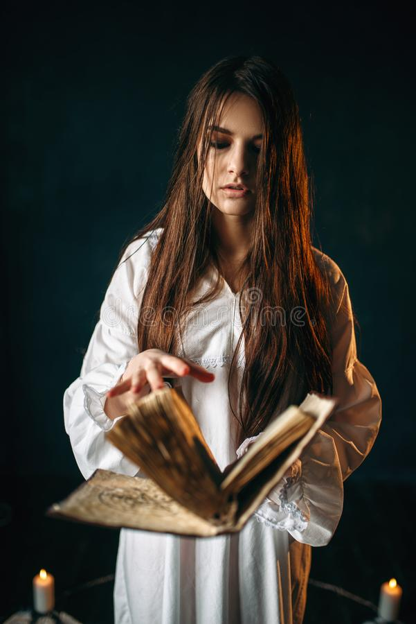 Woman sitting in the center of pentagram circle. Young woman in white shirt sitting in the center of pentagram circle with candles and reads a spell, black stock photography