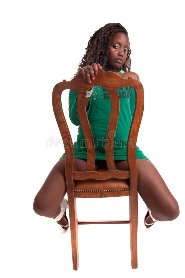 Woman sitting on a chair. Beautiful woman sitting on a chair, isolated royalty free stock photo