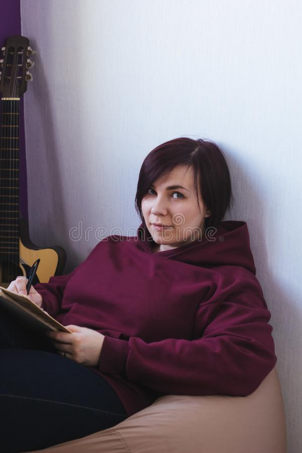 woman sitting on a chair and compose a new song stock image