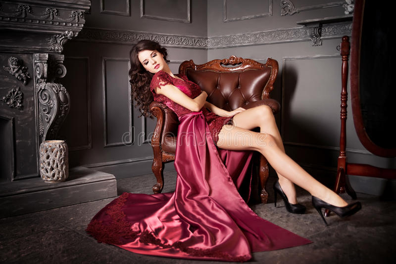 Woman sitting in chair in long claret, purple dress. Luxury. Indoor royalty free stock images