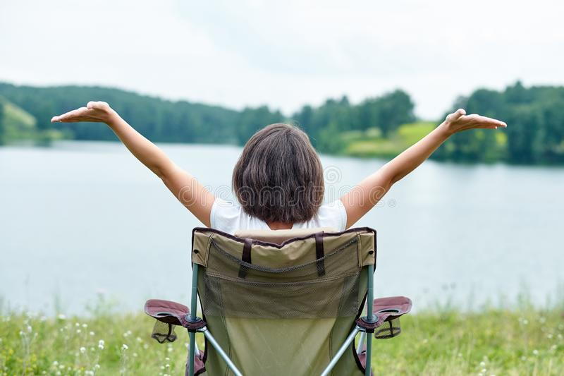 Woman sitting on chair in nature near the lake. Outdoor relaxing in summer. Raising your Hands up royalty free stock photography