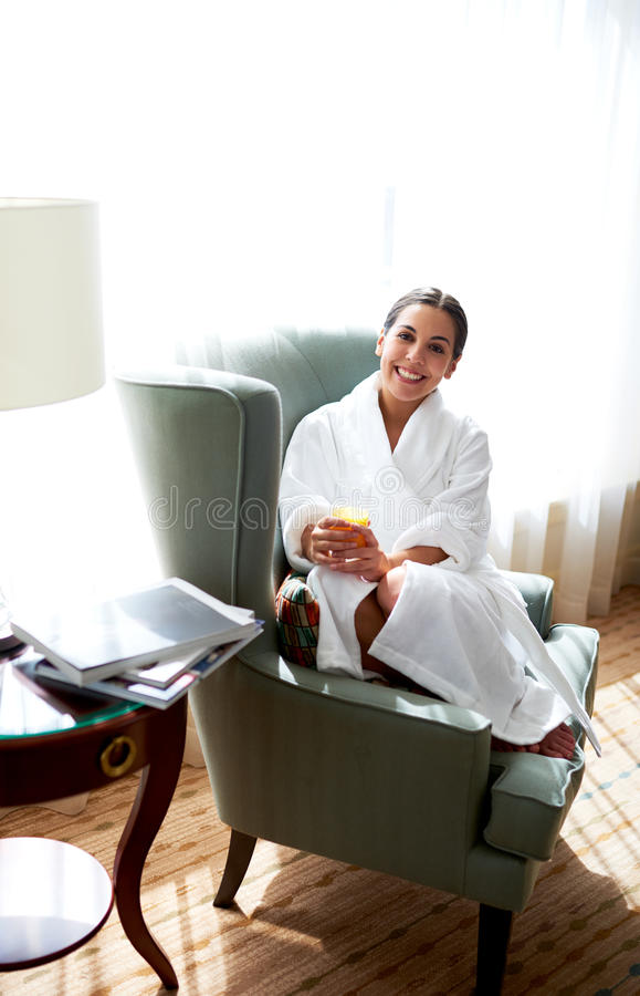 Woman sitting in chair relaxing. Angled view of woman curled up in chair smiling and holding glass of orange juice royalty free stock image