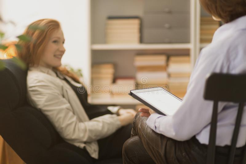 Woman during psychotherapy. Woman sitting in a chair and talking to a therapist during psychotherapy stock images