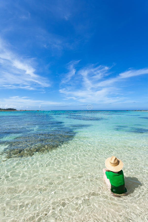 Woman sitting in clear shallow water of a tropical beach, Amami Oshima Island, Japan royalty free stock image