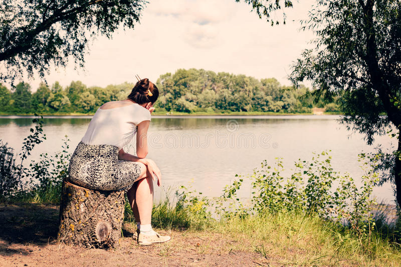 Woman Sitting Close to the River stock image