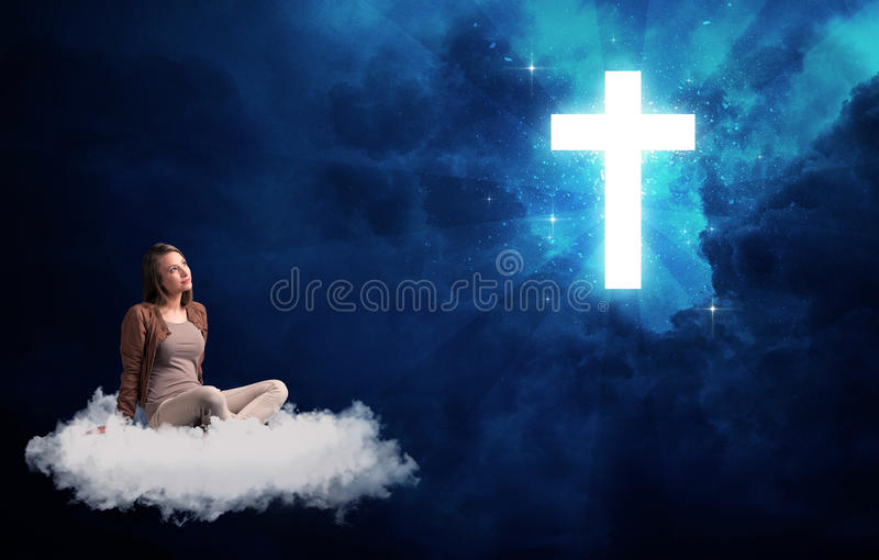 Woman sitting on a cloud looking at a cross. Caucasian woman sitting on a white fluffy cloud looking at a big, bright; blue; glowing cross stock photography
