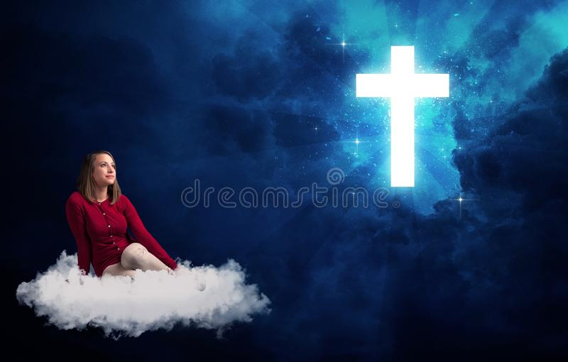 Woman sitting on a cloud looking at a cross. Caucasian woman sitting on a white fluffy cloud looking at a big, bright; blue; glowing cross royalty free stock photo