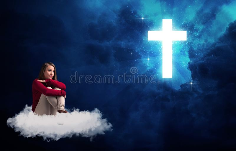Woman sitting on a cloud looking at a cross. Caucasian woman sitting on a white fluffy cloud looking at a big, bright; blue; glowing cross royalty free stock photography