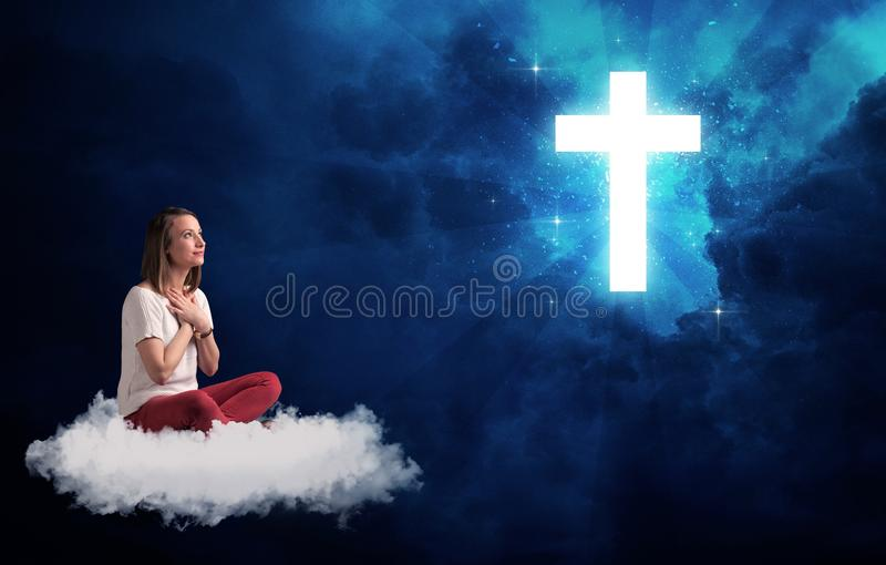 Woman sitting on a cloud looking at a cross. Caucasian woman sitting on a white fluffy cloud looking at a big, bright; blue; glowing cross royalty free stock photos