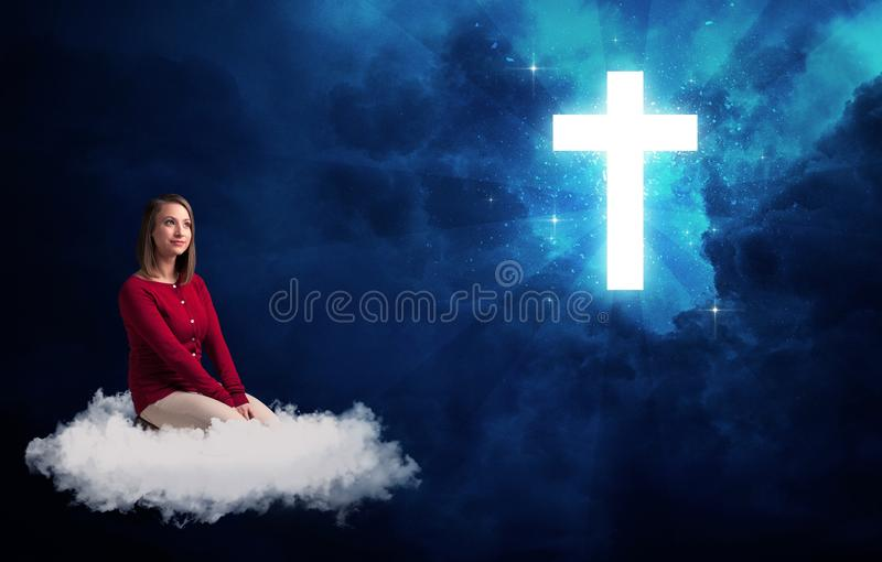 Woman sitting on a cloud looking at a cross. Caucasian woman sitting on a white fluffy cloud looking at a big, bright; blue; glowing cross stock photos