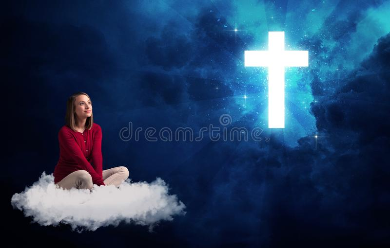 Woman sitting on a cloud looking at a cross. Caucasian woman sitting on a white fluffy cloud looking at a big, bright; blue; glowing cross stock photo