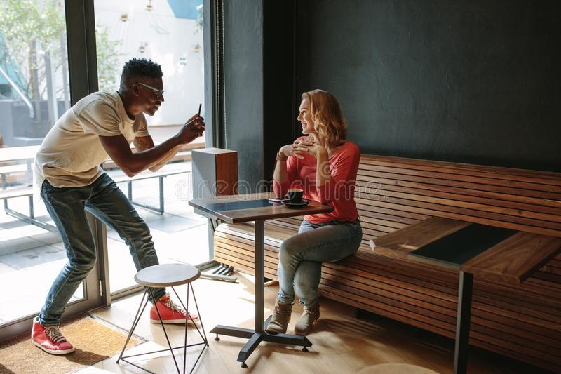 Friends at a coffee shop. Woman sitting at a coffee shop posing for a photograph. Man taking photo of a women using mobile phone at a coffee shop stock photos
