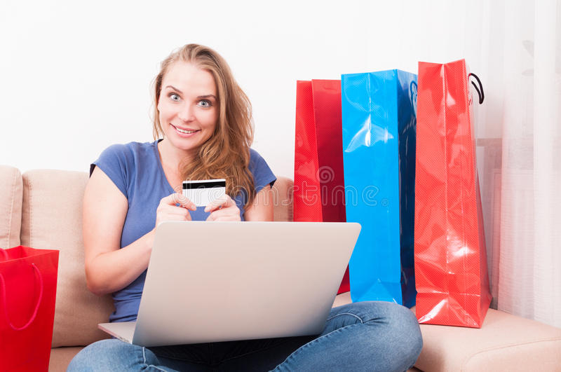 Woman sitting on couch holding laptop and card being excited. Woman sitting on couch holding laptop and card being very excited with shopping bags around stock images