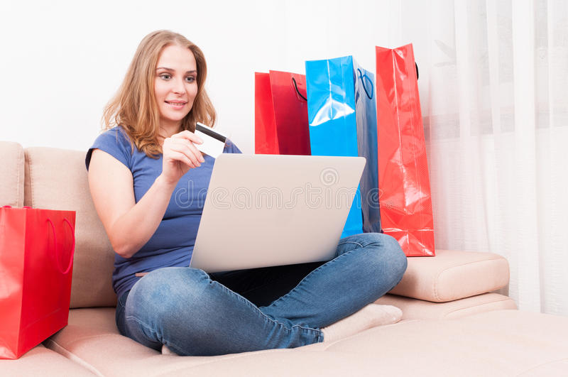 Woman sitting on couch holding laptop and card. With shopping bags around stock photos