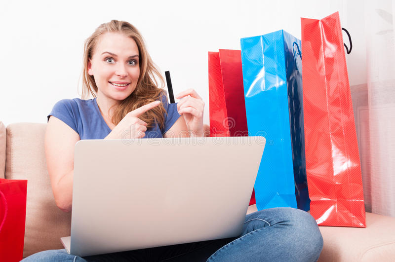 Woman sitting on couch holding laptop pointing card. Woman sitting on couch holding laptop pointing a credit or debit card and looking excited with shopping bags royalty free stock photography