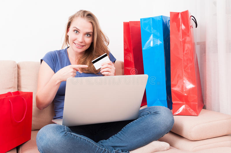 Woman sitting on couch holding laptop pointing card. Woman sitting on couch holding laptop pointing a credit or debit card with shopping bags around stock images