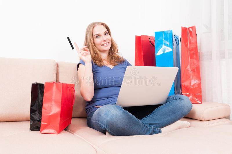 Woman sitting on couch holding laptop showing card. With shopping bags around royalty free stock images