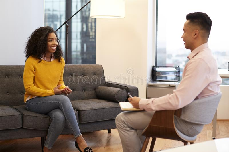 Woman Sitting On Couch Meeting With Male Relationship Counsellor In Office stock photos