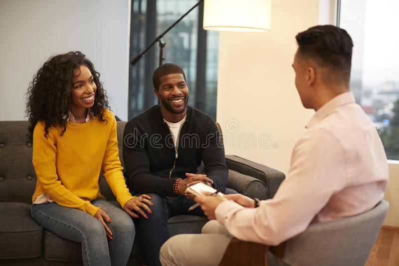 Woman Sitting On Couch Meeting With Male Relationship Counsellor In Office stock images