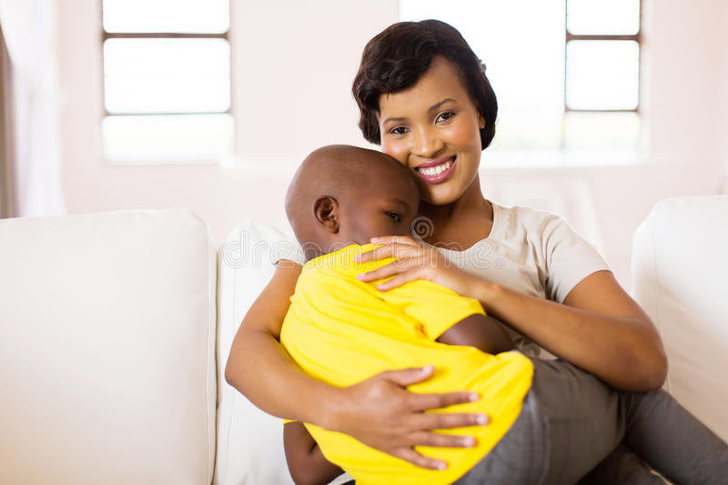 Woman sitting couch son. Attractive young african women sitting on couch with her son royalty free stock photography