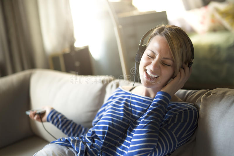 Woman sitting on the couch take some good time with music headphone, royalty free stock photo