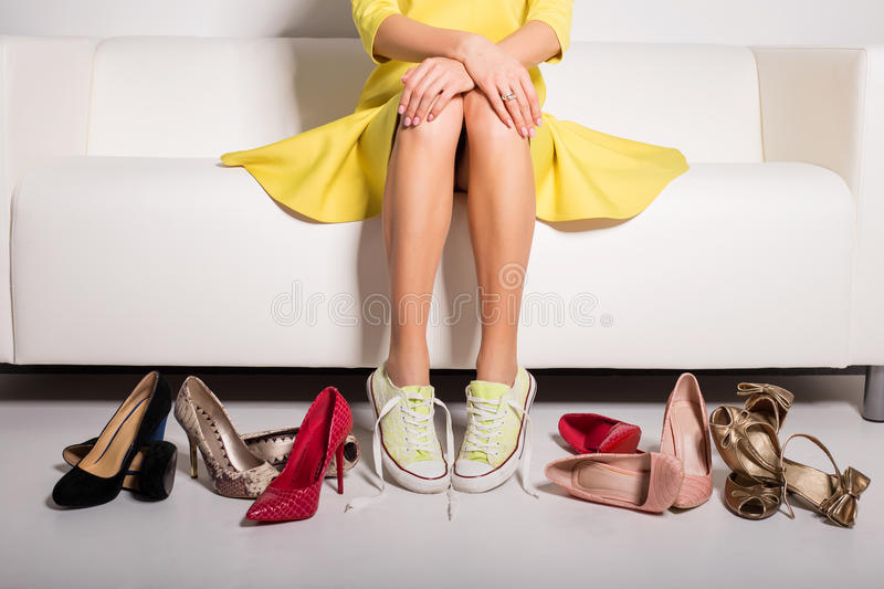 Woman sitting on couch and trying on shoes. Woman sitting on couch and trying on many different pairs of shoes royalty free stock photo