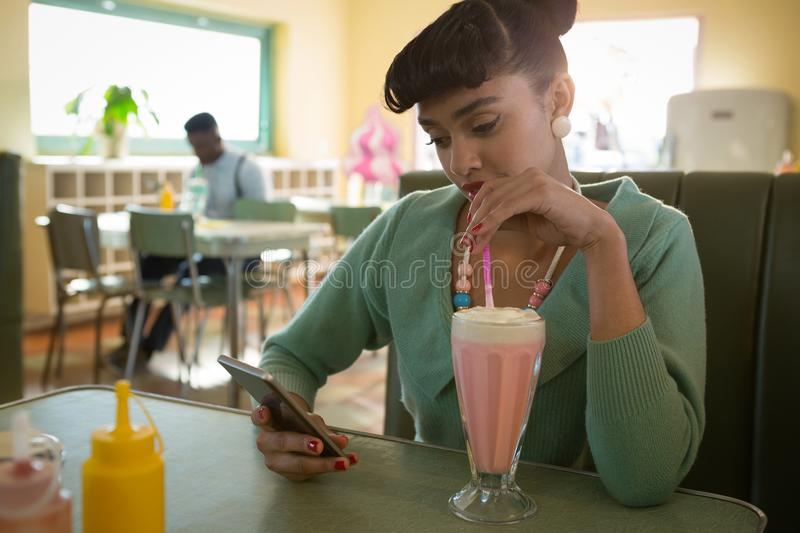 Woman sitting on couch using her mobile while having milkshake royalty free stock photos