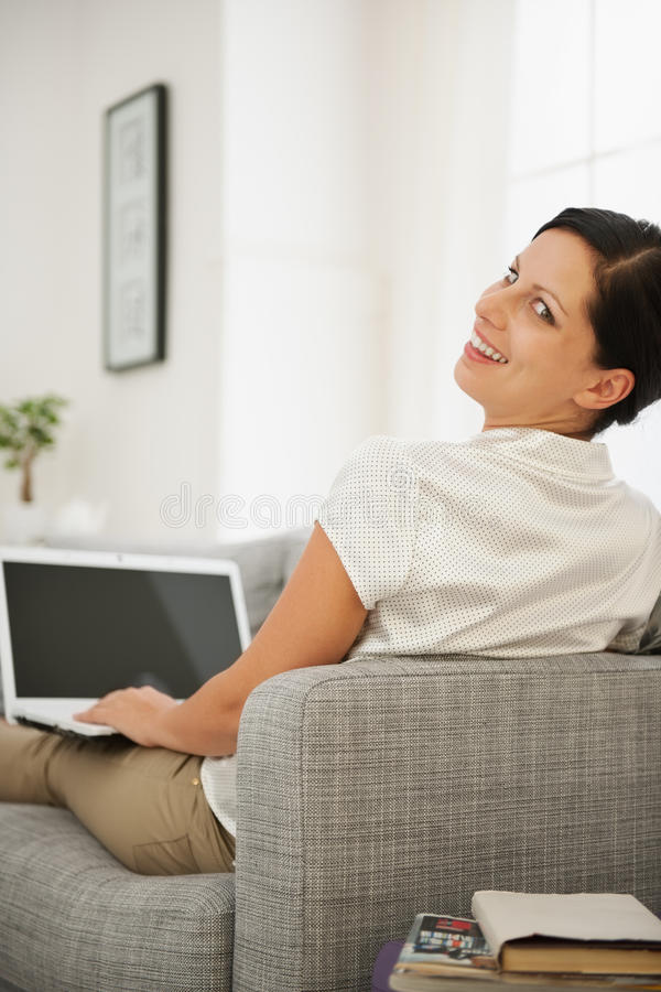 Woman Sitting On Couch And Working On Laptop Royalty Free Stock Photo