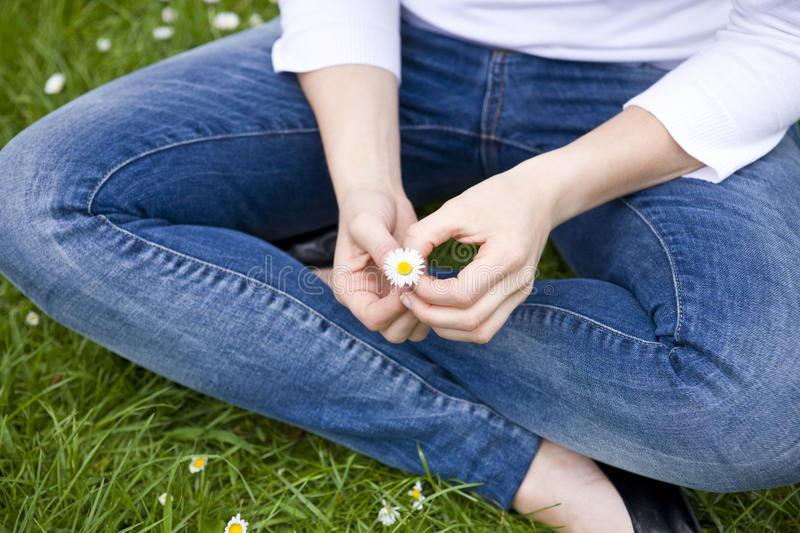 A woman sitting cross-legged, holding a daisy stock images