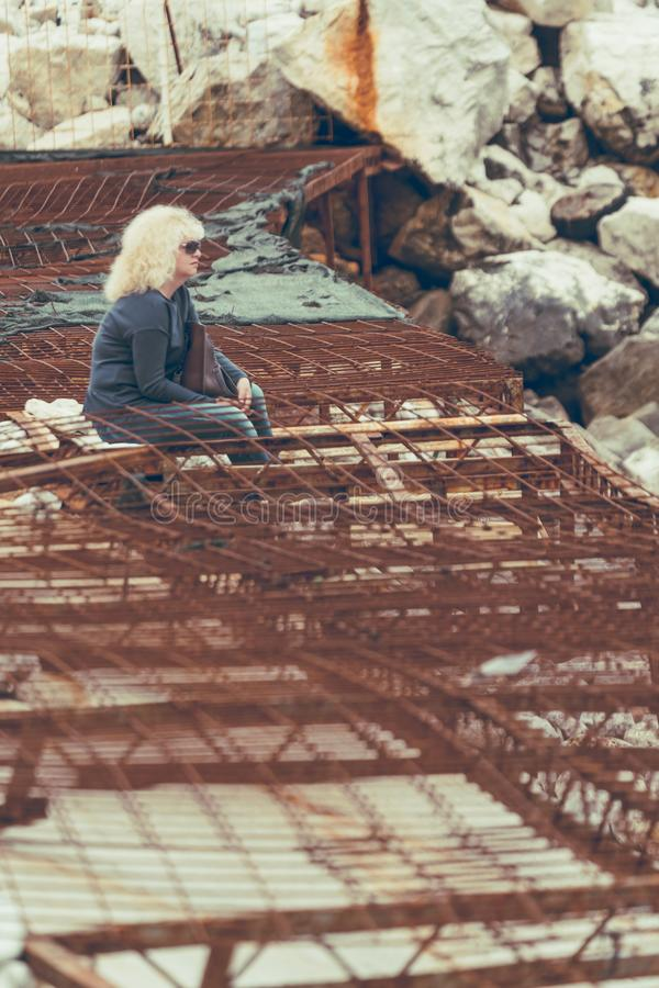 Woman sitting on damaged concrete and steel stock images