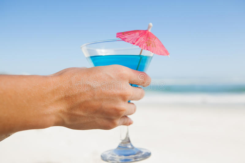 Woman sitting in deck chair with a cocktail at the beach. On a sunny day royalty free stock photo