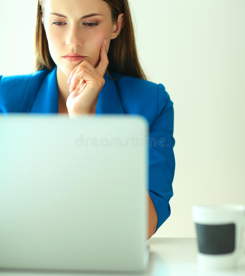 Woman sitting on the desk with laptop stock image