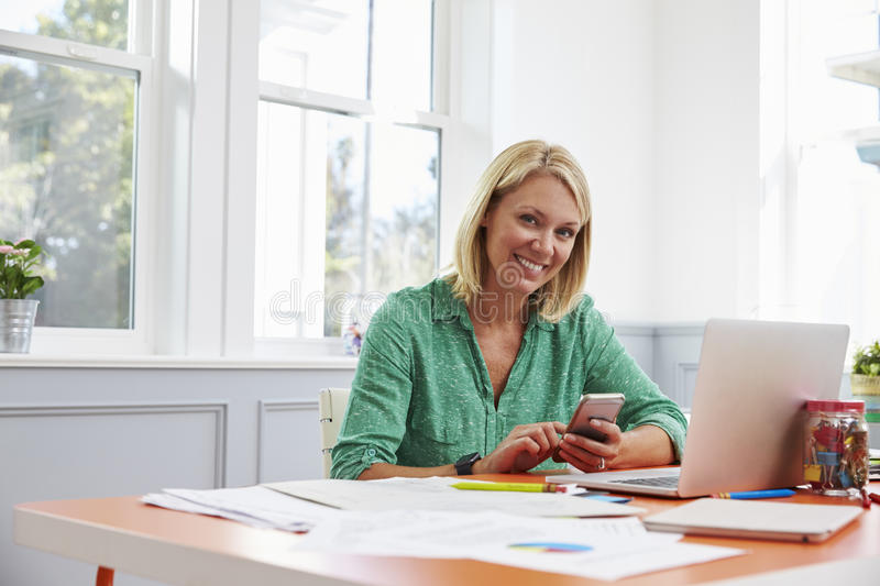Woman Sitting At Desk Using Mobile Phone In Home Office stock image