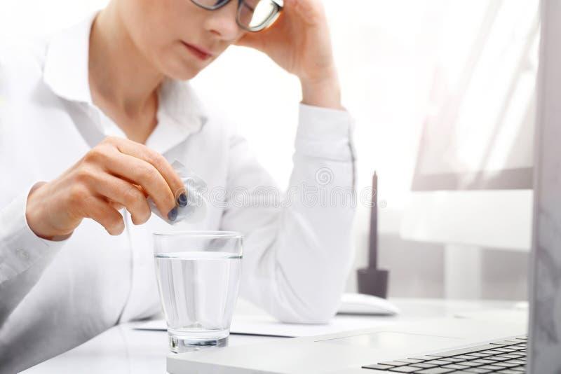 Painkiller tablet. A woman at work dissolves the effervescent painkiller tablet. stock photos