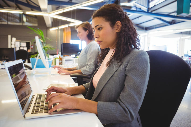 Woman sitting at desk and working on laptop stock photo