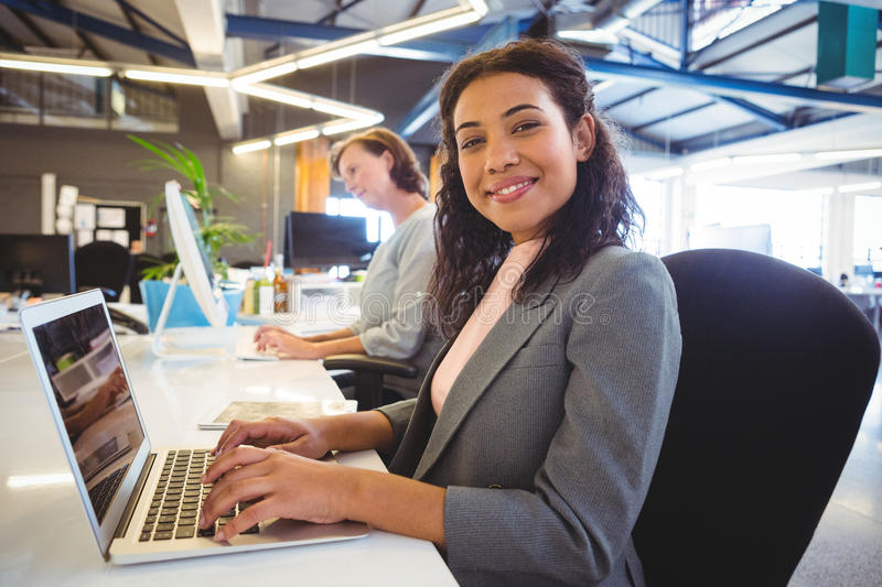 Woman sitting at desk and working on laptop stock image