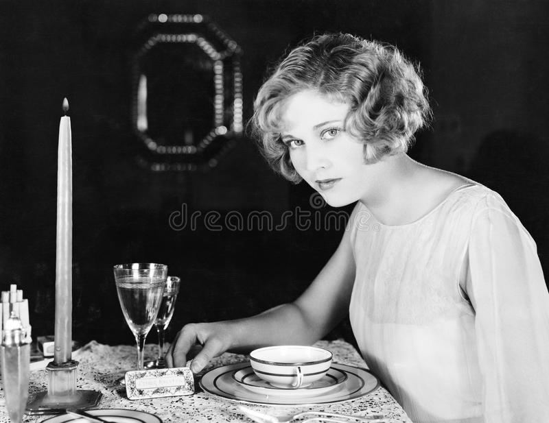Woman sitting at the dinner table stock photography