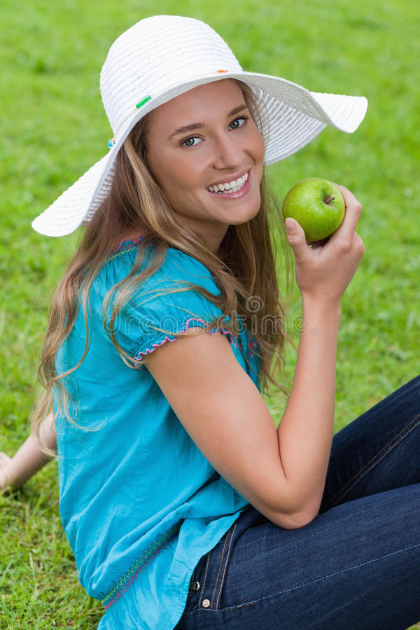 Woman Sitting Down While Eating An Apple Royalty Free Stock Photo
