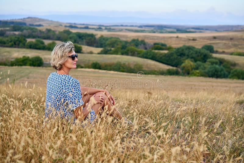 Woman sitting in dry barren grass looking away royalty free stock photos