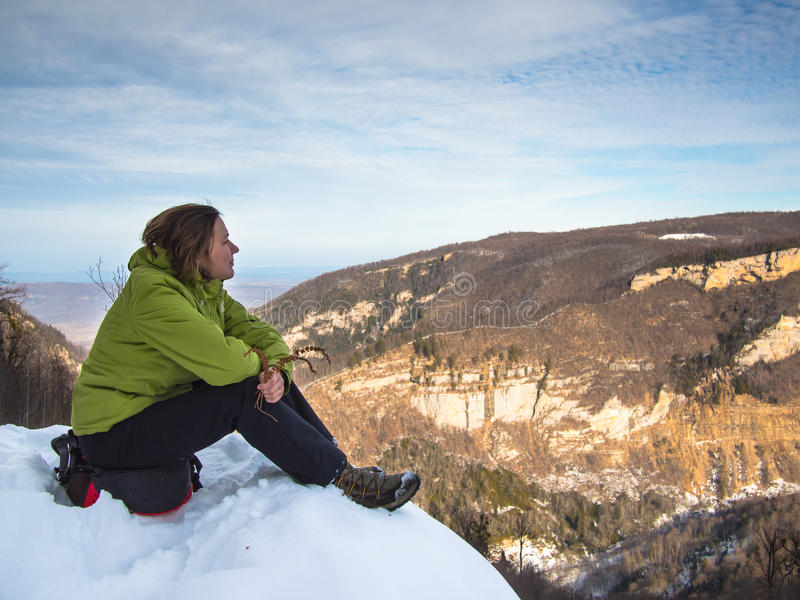 Woman sitting on the edge of the cliff stock photography