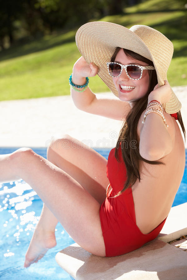 Woman Sitting On Edge Of Swimming In Pool Stock Photos