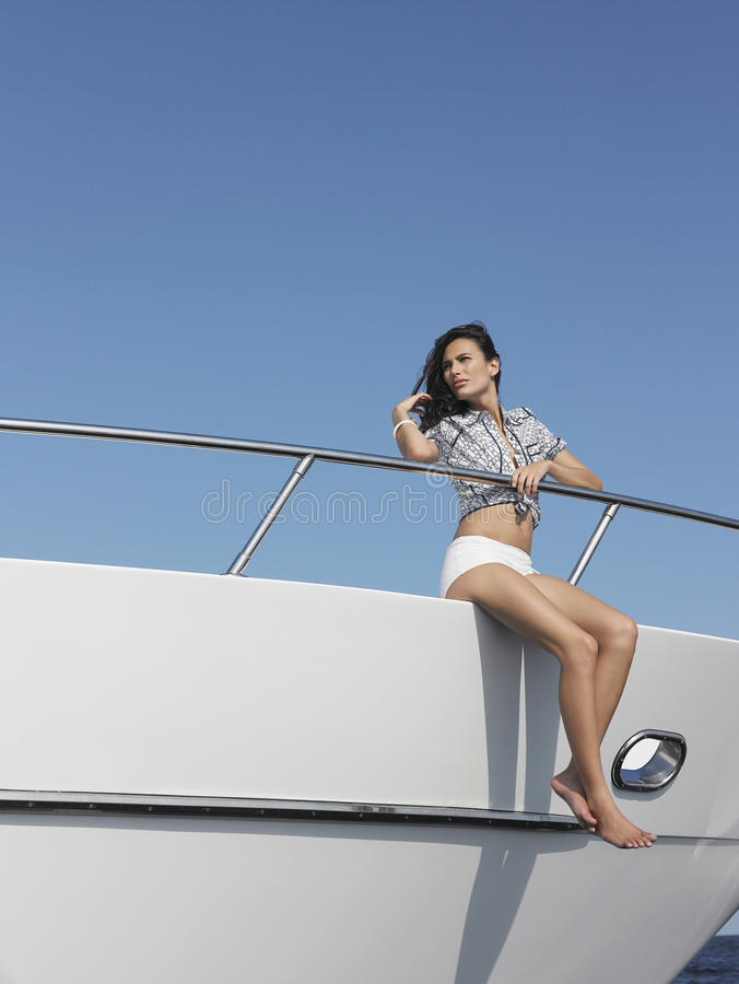 Woman Sitting At Edge Of Yacht stock photo
