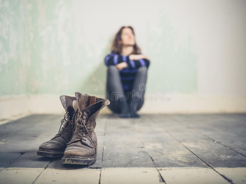 Woman sitting in empty room with boots royalty free stock photos