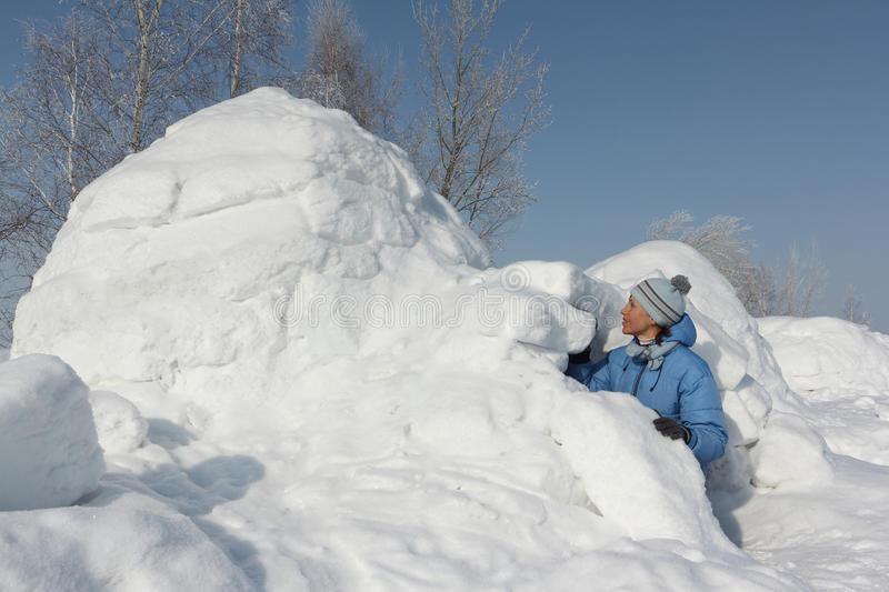 The woman sitting at an entrance to an igloo stock photography