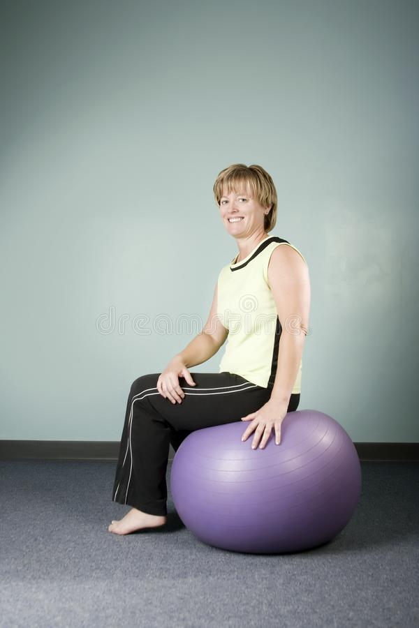 Woman Sitting on an Exercise Ball royalty free stock photo