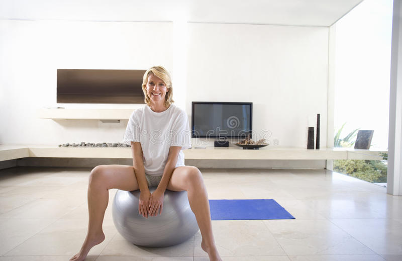 Woman sitting on exercise ball in living room, smiling, portrait royalty free stock photo