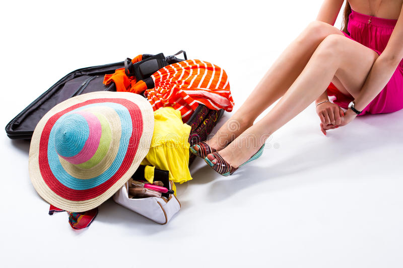 Woman sitting beside filled suitcase. royalty free stock image