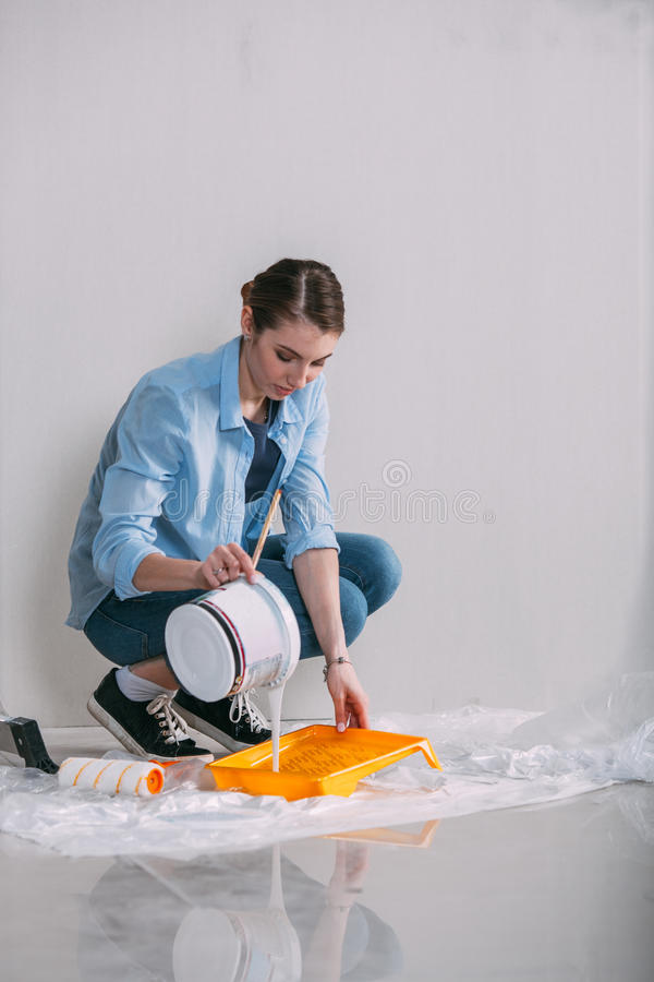 Woman sitting on the floor and mixing wall paint stock images
