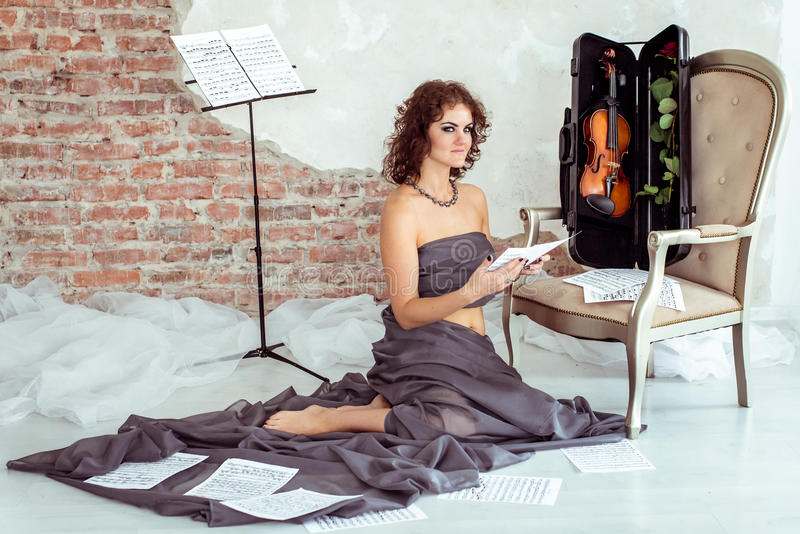 Woman sitting on the floor near the chair with violin royalty free stock photography