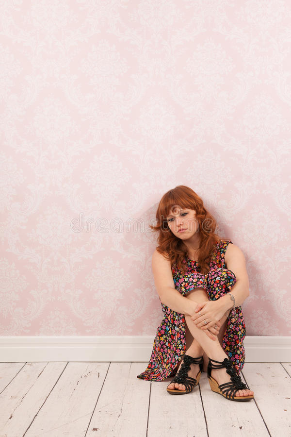 Sad Woman Sitting At Te Floor In Room With Vintage Wall Paper